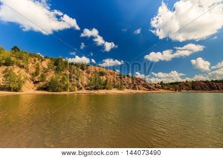Quarry Or Lake Or Pond With Sandy Beach, Water, Trees And Hills With Cloudly Sky