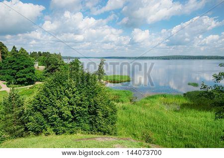 View from the hill to the lake with clouds reflected in the water