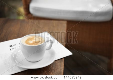 Cup of fresh coffee and morning newspaper on wooden table