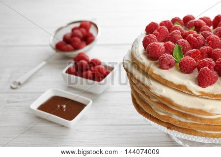Tasty raspberry cake on the stand, wooden background