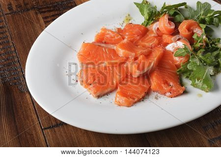 Smoked trout with greens on a white plate. Wooden background.