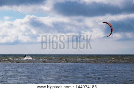 Kitesurfer on blue sea and sky background.