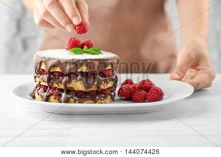 Woman decorating berry cake with raspberries