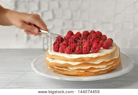 Woman cutting berry cake, closeup