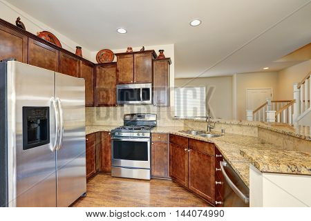 Kitchen Interior With Steel Appliances And Granite Counter Tops