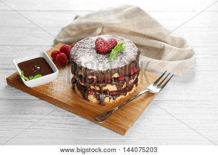 Tasty raspberry cake with fresh berries and chocolate in bowl on wooden background