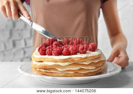 Woman cutting berry cake, closeup