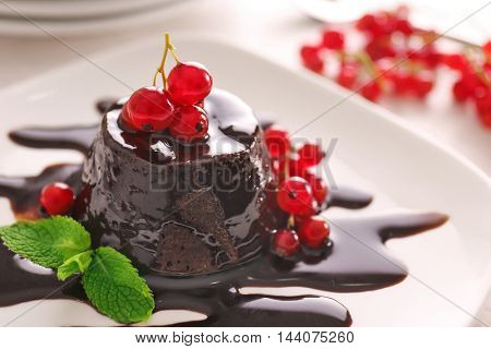 Chocolate fondant cake with fresh red currant on the plate