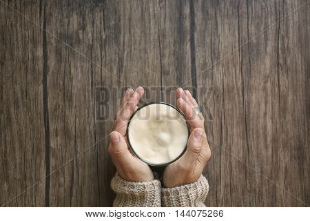 Female hands holding cup of green matcha tea on wooden background