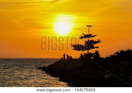 Silhouette of group of fisherman hanging out and enjoying sunset at Labuan island beach,Malaysia.