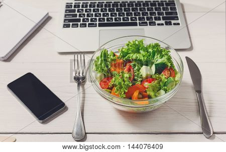 Healthy business lunch in the office, top view of vegetable salad on white wooden desk near laptop computer keyboard. Salad bowl, mobile phone and notepad on table. Snack at break time