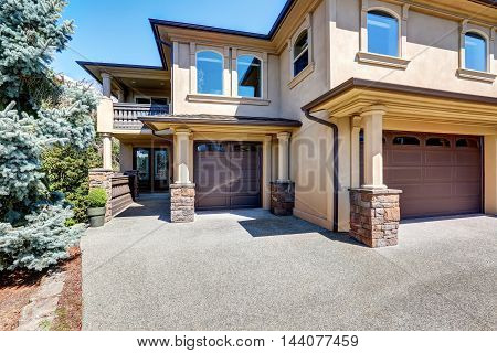 Luxury House Exterior With Columns And Brown Garage Doors.