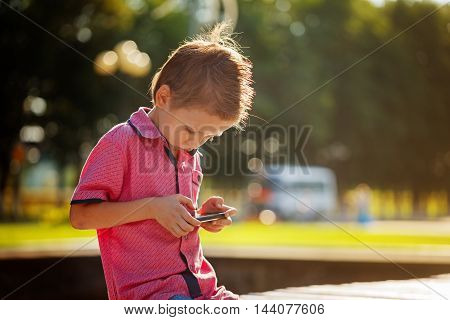 Little kid absorbed into his phone for playing in warm sunny day outdoors