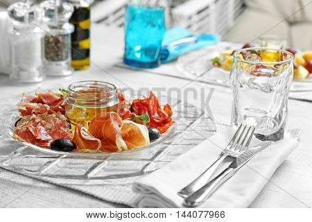 Plate with tasty meat snacks on wooden table in cafe