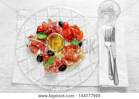 Plate with tasty meat snacks on wooden table