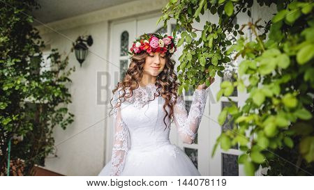 Bride with wreath standing outside in front of a door