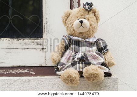 girl teddy bear sitting outside a home at window  architrave walls