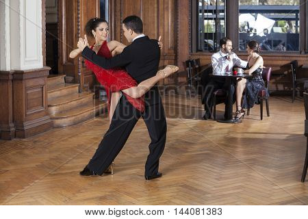 Tango Dancers Performing Piernazo While Mid Adult Couple Dating