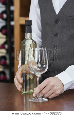 Bartender With White Wine And Glass At Counter