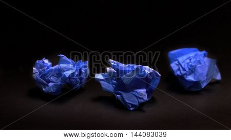 Crumpled blue paper ball isolated on a black background