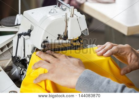 Tailor Sewing Fabric At Workbench