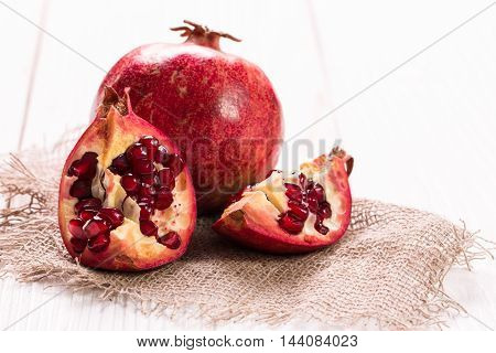 Some red juicy pomegranate whole and broken on rustic wooden table