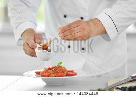 Chef preparing delicious pasta in kitchen