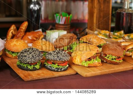 Wooden cutting boards with different burgers on counter