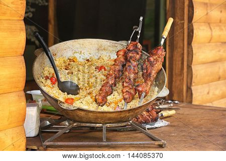 Delicious pilaf in iron pan and barbecue skewers with juicy meat on table