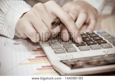 business man hand with Calculator and business report.