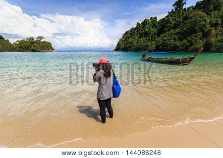 Beautiful woman taking photos at tropical beach Phuket Thailand