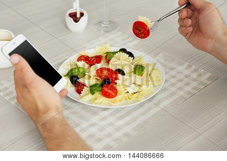 Man eating delicious pasta in restaurant