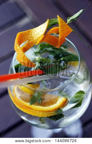 Glass of lemonade on wood.Glass of water with fresh lemon, orange,ice and mint