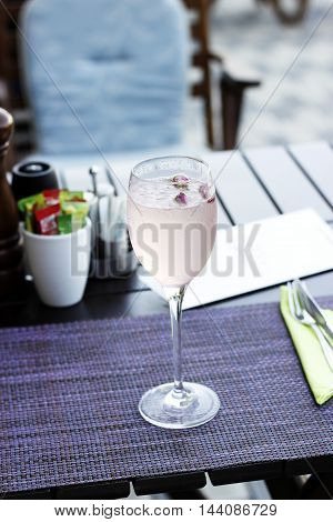 Glass of lemonade on wood.Glass of water with frose flowers and ice