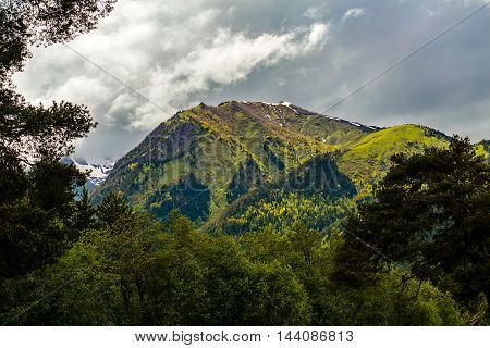 Beautiful mountain peak in the clouds forest-covered under harsh sky