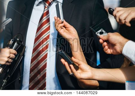 Journalists interviewing politician, toned image, close up, unrecognizable people