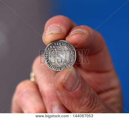 picture of a Fingers hold old coin from France silver coin of King Louis XIV