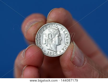 picture of a Fingers hold old coin from switzerland