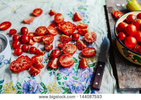 Tomato on wooden table. Freshly Picked red Tomatoes. Variation of tomatoes on wooden surface. Vegetables in the section. Harvesting. Healthy food from the garden.