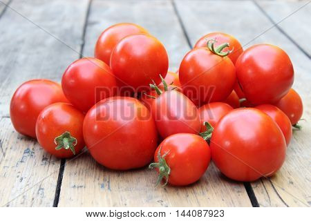 Red tomatoes scattered on background of boards