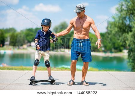 Little boy learning snakeboard grandpa helping, toned image
