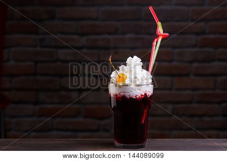Alcoholic Cocktail Standing On A Wooden Table . With A Straw And Yellow Cherry .