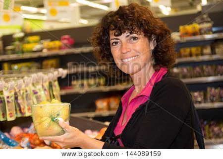 Woman In Supermarket At The Vegetable Shelf Shopping For Groceries,