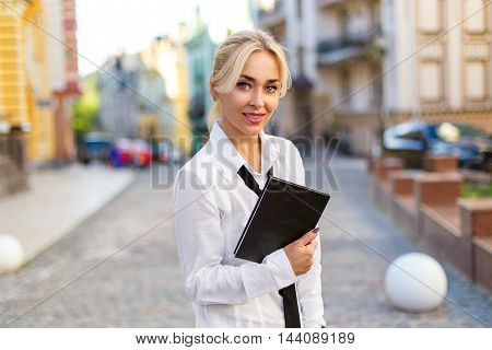 Beautiful smiling business woman with book in white shirt on the street outdoor