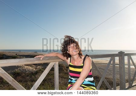 Outdoor portrait of a brunette woman in her forties taken at the beach with the sea behind her