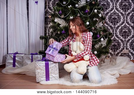 beautiful young woman opening gifts. The concept of New Year and Merry Christmas