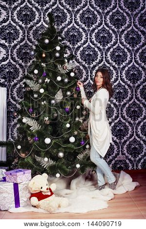 beautiful young woman decorates a Christmas tree. The concept of New Year and Merry Christmas