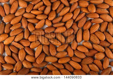 Pile of almonds close-up as abstract food background. Lots of peeled brown nut seeds