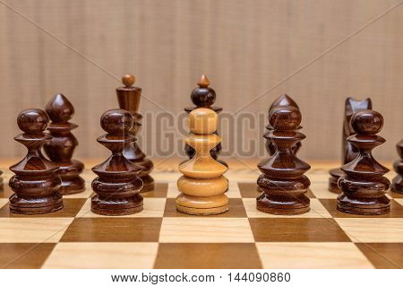 White pawn standing in a row of black pawns