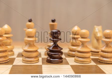Black pawn is among white pawns on the chessboard